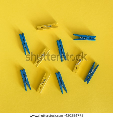 Colored wooden clothespins on yellow background. Top view. - stock photo