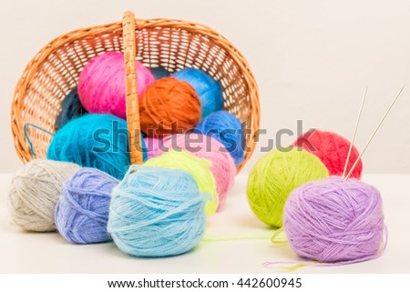 colored woolen thread crumbled from wicker basket close up on a white background