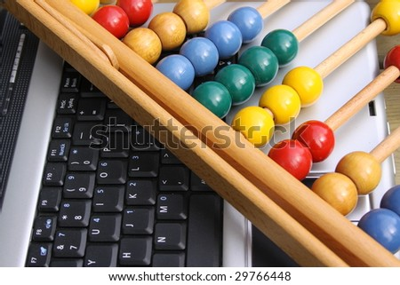 Colorful abacus laying on a laptop keyboard - stock photo