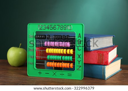 Colorful abacus with stack of book sand green apple on desk on green chalkboard background - stock photo