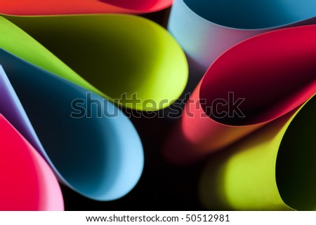 Colorful abstract and macro image of card stock in unique elliptical shapes with shadow effect and selective focus on a black background. - stock photo
