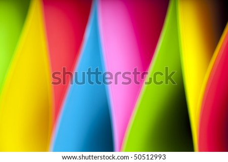 Colorful abstract and macro image of card stock in unique elliptical shapes with shadow effect and selective focus on a black background.  Image taken with slight blur for additional effect. - stock photo