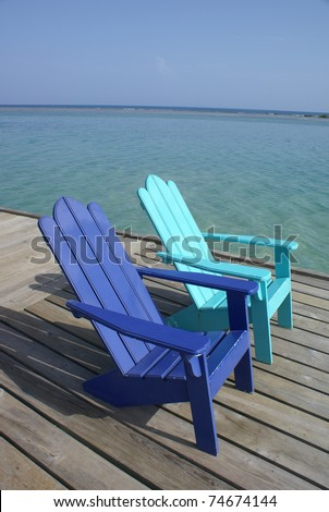 colorful adirondack chairs sit on a dock by the Caribbean sea - stock photo
