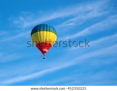 Colorful air balloon ascending in blue sky