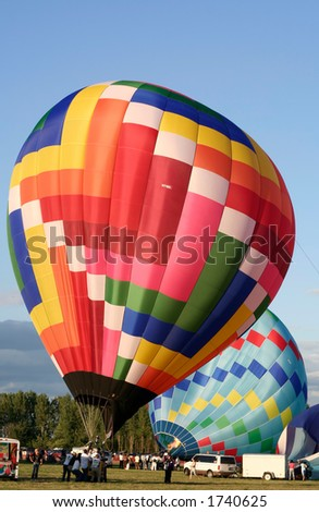 Colorful air balloons preparing for launch - stock photo