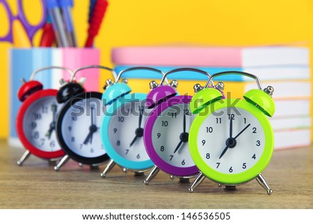 Colorful alarm clock on table on yellow background