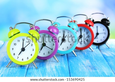 Colorful alarm clocks on table on blue background - stock photo