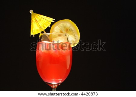 Colorful alcoholic cocktail in a tall glass with lemon and umbrella against black background