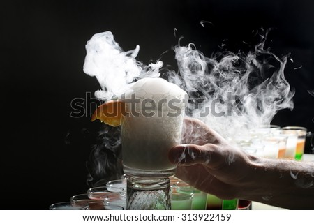 Colorful alcoholic shot cocktails in glasses and human hand holding one long beverage making reaction of white smoke standing in row on black studio background, horizontal picture - stock photo