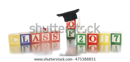 "Colorful alphabet blocks arranged to say ""Class of 2017.""   A miniature rolled diploma and graduation cap sits on top of the blocks. Isolated on white."