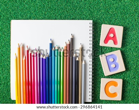 """Colorful alphabet letters """"abc"""" ,crayons and the note book on grass background - stock photo"""