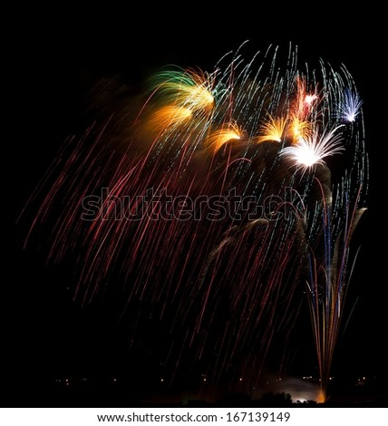 Colorful amazing fireworks explosion in dark sky background, 4 of July, Independence day, explode, fireworks festival fragment close up with village silhouette on the bottom, fireworks in Malta  - stock photo