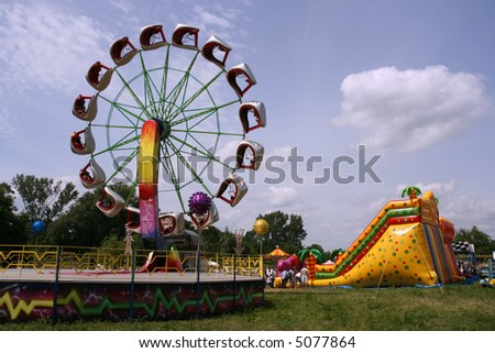 Colorful amusement park on a sunny summer day - stock photo