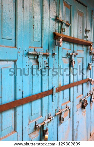 Colorful ancient door with many door locks - stock photo