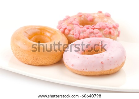 Colorful and delicious donut in white plate - stock photo