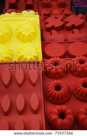 Colorful and differently shaped silicone baking pans on sale at market - stock photo
