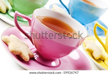 Colorful antique tea cups with tea - stock photo