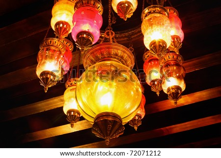 Colorful arabic lamp hanging from a wooden ceiling. Concept for arabic culture and design. - stock photo