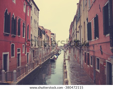 Colorful architecture and narrow canals of Venice, Italy on a cloudy spring day. Image filtered in faded, retro, Instagram style with extremely soft focus; nostalgic, vintage concept of travel.