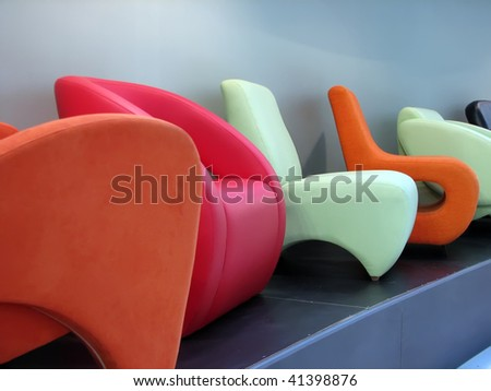colorful arm chairs on the exhibition. home furniture in various colors. - stock photo