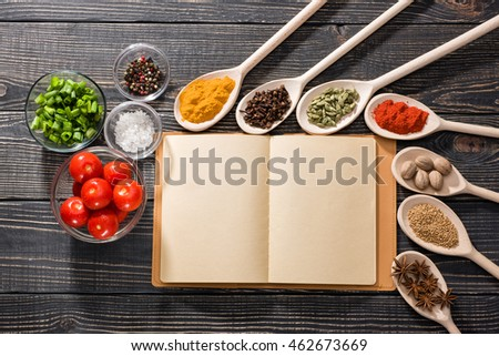 Colorful aromatic spices and open recipe book, on dark wooden background, view from the top