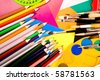 Colorful art supplies lying on cardboard - stock photo