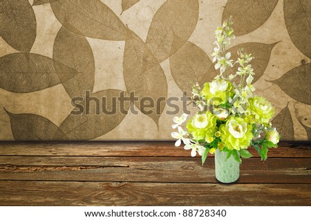 Colorful Artificial Flower Arrangement leaf and wood background - stock photo