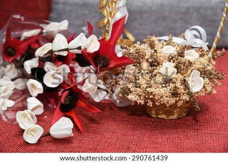 Colorful artificial flower made with paper and bamboo leaves.Basket full dried flowers with white and golden ribbon isolated on red jute background. Wedding Decoration floral bouquets of dried flowers - stock photo