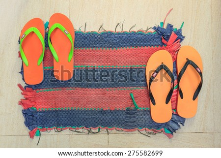 Colorful asian floor mat with flip flops on it - stock photo