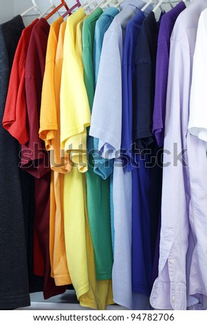 Colorful assortment of menswear shirts hanging from a clothes rack in a closet.