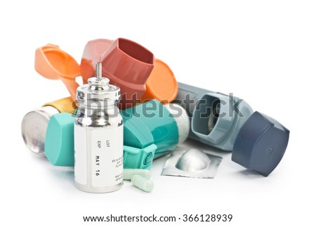 Colorful asthma inhalers and medication on white background. Albuterol sulfate is a common non trademarked medication name. - stock photo