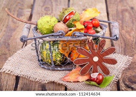 colorful autumn decoration on wooden table, a basket filled with autumn stuff (pumpkins, chestnuts, nuts, leaves and rose hips)