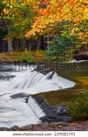 Colorful autumn foliage surrounds a cascade at Bond Falls, a very beautiful multistage waterfall in Michigan's western Upper Peninsula. - stock photo
