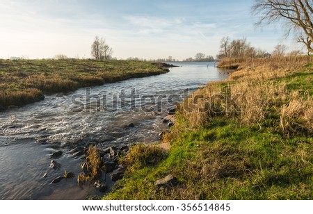 Colorful autumn landscape in the Netherlands with a small stream leading to a large river.