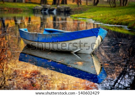 Colorful autumn landscape.Nature background.boat on the lake in autumn forest. Old wooden boat on the lake bank in autumn season.Autumn's Romanian lake - stock photo