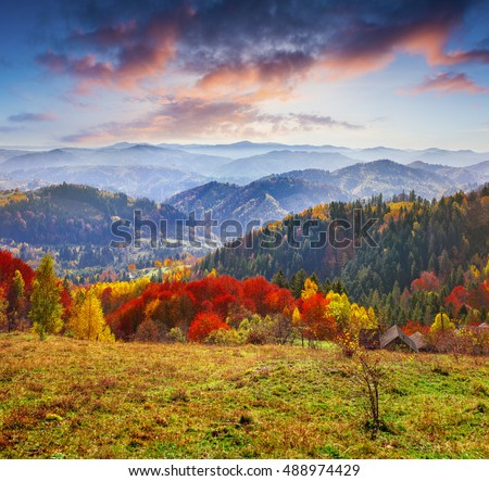 Colorful autumn morning in the Carpathians. Dramatic sunrise in the mountain village. Artistic style post processed photo.