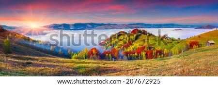 Colorful autumn panorama of the mountains. Foggy sunrise. - stock photo