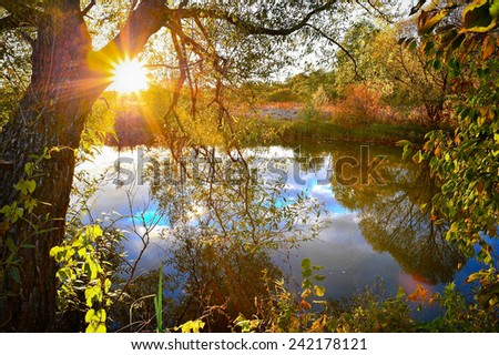Colorful autumn sunset on the river with sun rays - stock photo
