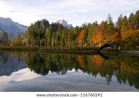 colorful autumn trees mirroring in the mountain lake - stock photo
