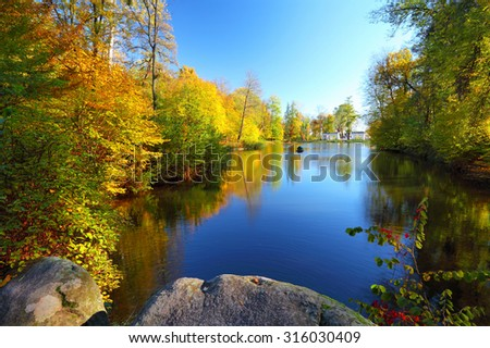 Colorful autumn trees near the river in park. Blue sky reflected in calm water. Landscape in sunny day - stock photo