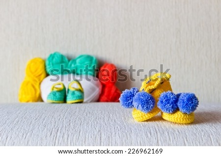 Colorful baby bootees with colored wool on white linen background - stock photo