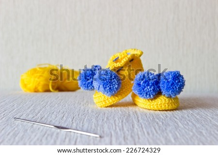 Colorful baby shoes with wool and knitting needles on white background - stock photo