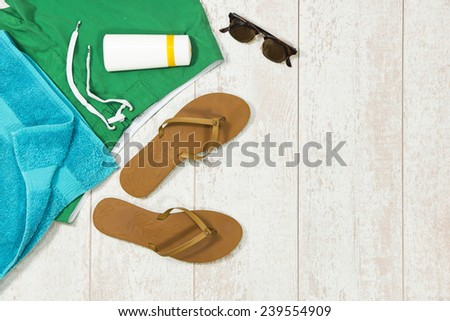 Colorful background image with basic summer vacation items, such as swimming shorts, a towel, sunglasses, sun block and flip flop slippers - stock photo