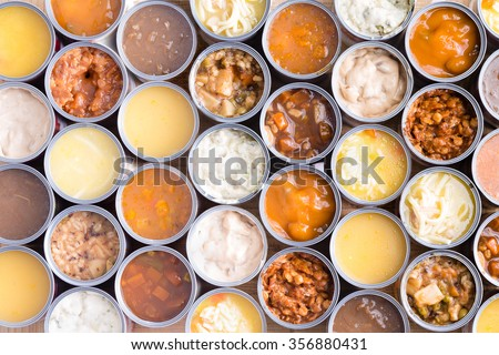 Colorful background of neatly arranged rows of opened cans of assorted soup viewed full frame from above in a food abstract still life - stock photo