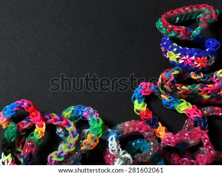 Colorful background rainbow colors rubber bands loom bracelets on black background. Copy space. Trendy kids' fashion accessories. - stock photo