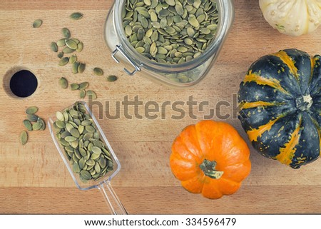 Colorful background with pumpkin seeds and squash over wooden background