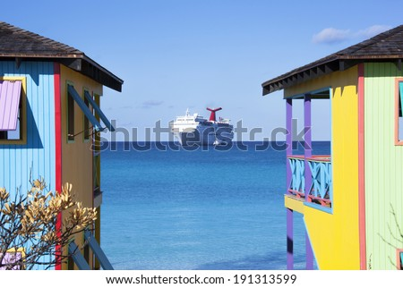 Colorful Bahamian houses with a cruise ship in a background (Half Moon Cay). - stock photo