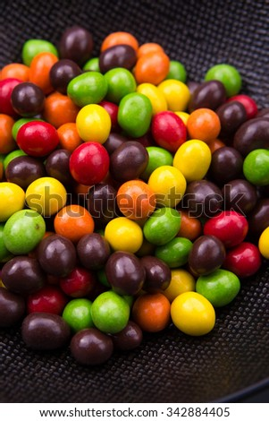 colorful ball chocolate candy on black background - stock photo