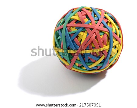 Colorful ball composed of rubber bands wound around each other and interwoven to keep the round shape in red, blue , yellow and green on a white background with shadow - stock photo