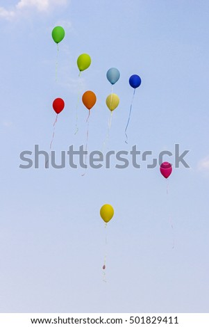 Colorful balloons are rising before blue sky